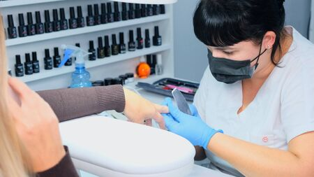 Manicurist files a nail with a nail file to a client. Manicure process, nail extension. close-up.