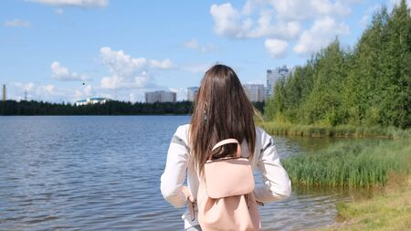 brunette girl with a backpack enjoys stunning scenic views. Lake and beautiful landscape. Adventure, freedom, lifestyle.