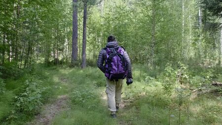 man with a large tourist backpack traveling through the woods, ecotourism concept