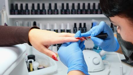 Manicurist puts red gel polish on the nails of a client in a beauty salon.