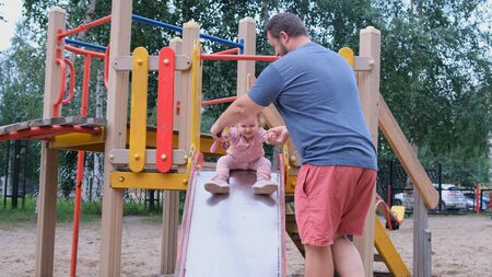 Dad and daughter play in the playground, a man catches a daughter who moves down from a childrens slide