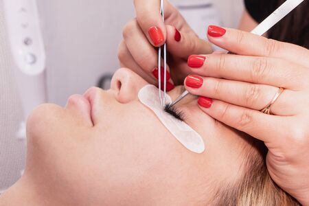 Eyelash Extension Procedure. Woman Eye with Long false Eyelashes. Closeup macro shot of fashion eyes in beauty salon. Hands beautician