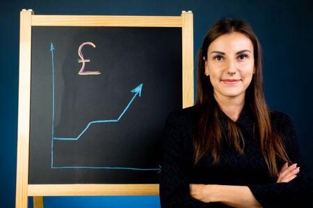 Pound arrow chart of growth is drawn on a black chalk board, a happy woman is standing nearby.
