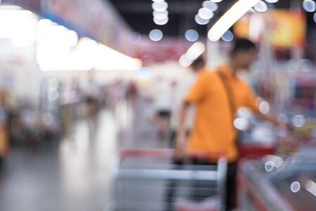 Abstract blurred supermarket aisle with colorful shelves and unrecognizable customers as background Stockfoto