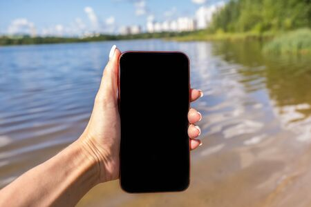 Mockup image of a woman using smart phone with blank black screen at outdoor and lake nature background Stockfoto