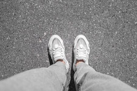 white sneakers walking on concrete. Sneakers on the pavement. Top view of legs on asphalt Stockfoto