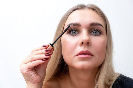 Headshot of female with bright makeup applying mascara on eyelashes