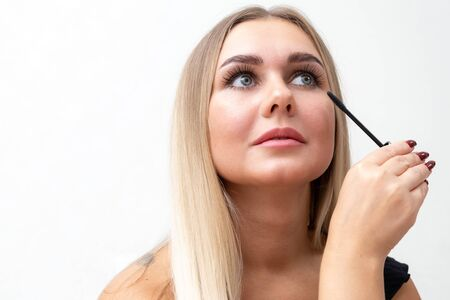 Beautiful blonde woman paints eyelashes. Beautiful female face. Makeup Read More Beauty girl with perfect skin. Makeup in progress.