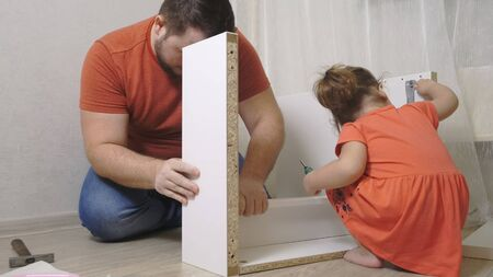 daughter with dad assemble white furniture together. Close up