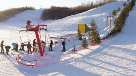 Ski lifts durings bright winter day. Skiers and snowboarders climb the mountain using a ski lift.