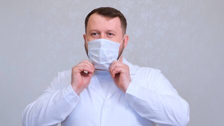 bearded male doctor is trying to put on a protective mask . Hygiene concept. prevent the spread of germs and bacteria and avoid infection with the crown virus.