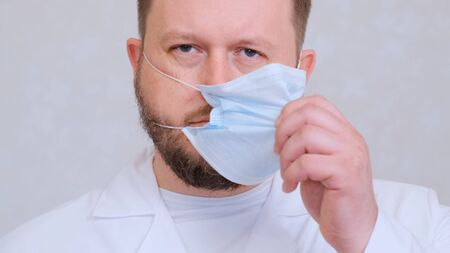bearded male doctor takes off his protective mask with a sad look. This is the end. Hygiene concept. prevent the spread of germs and bacteria and avoid infection with the crown virus. 스톡 콘텐츠