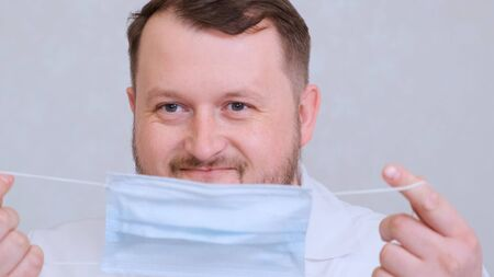 bearded male doctor is trying to put on a protective mask and get mad at her. Hygiene concept. prevent the spread of germs and bacteria and avoid infection with the crown virus.