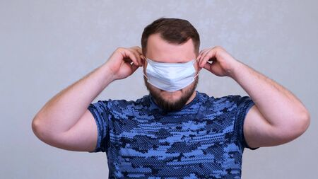 man puts on a protective mask. Hides his eyes. concept prevent the spread of germs and bacteria and avoid infection with the crown virus. 스톡 콘텐츠