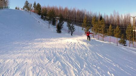 Top view snowboarders and skier climb the mountainside on a special lift in a winter sunny day. The concept of skiing and snowboarding