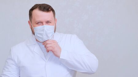 Male in a protective mask and a white shirt looks at the camera, close-up. Hygiene concept. prevent the spread of germs and bacteria and avoid infection with the crown virus. copy space.