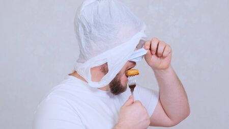 bearded man in a bag on his head and a protective mask has a cutlet from a fork. Fear of infection. Psychological assistance in case of panic. Joke situation. Imagens - 144232694