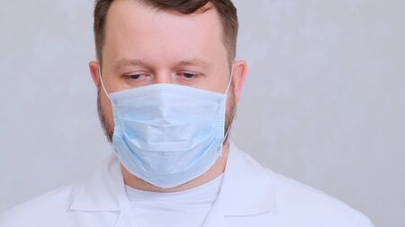 sad and upset Male in a protective mask and a white shirt looks at the camera, close-up. Hygiene concept. prevent the spread of germs and bacteria and avoid infection with the crown virus. copy space.