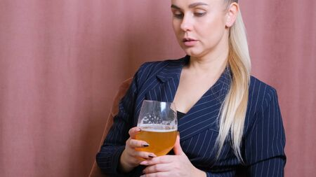 Female alcoholism for young blond woman holding bubbly wine, beer. Woman relaxing after work by drinking wine in the kitchen.