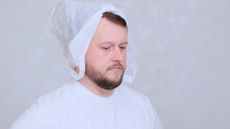 bearded man in a bag on his head. Fear of infection. Coronavirus COVID-19 Pandemic, home self-isolation and quarantine