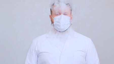 male in white clothes smokes an electronic cigarette through a protective medical mask. Protection against viruses, coronaviruses, lung diseases.