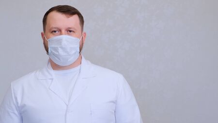 man in a protective mask and a white shirt looks at the camera, close-up. Hygiene concept. prevent the spread of germs and bacteria and avoid infection with the crown virus. copy space. 스톡 콘텐츠