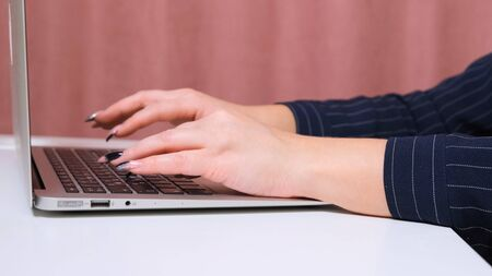 Close up of female hands while typing on laptop 스톡 콘텐츠