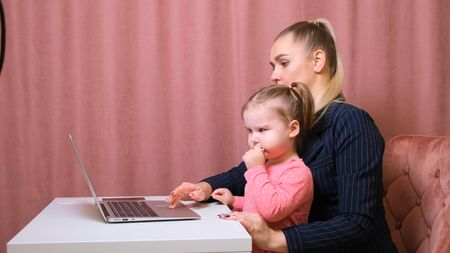 young beautiful blonde and her charming little daughter are shopping online with a laptop and credit card. Shopping in the online store 스톡 콘텐츠