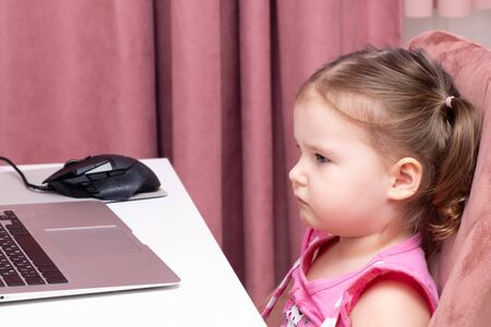 Beautiful cute sad little girl at a laptop. The concept of online learning with a laptop, distance learning, self-education.