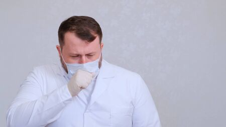 Doctor male coughs in a protective mask infected with a virus or coronavirus