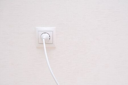 White electrical plug in the electric socket on a wall 스톡 콘텐츠