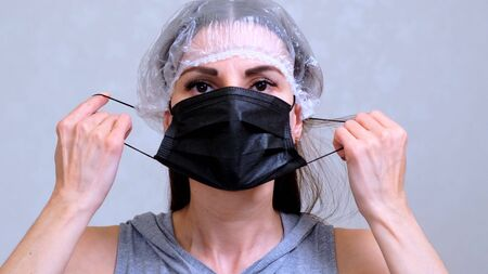 Female patient in a disposable cap puts on a black protective mask. Hygiene concept. prevent the spread of germs and bacteria and avoid infection with the crown virus.