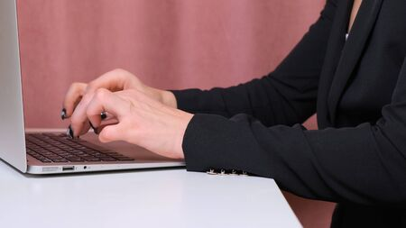 Close up of female hands while typing on laptop Imagens