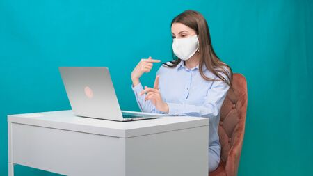 female in a protective mask is talking via video calling showing fingers on a laptop in the workplace or at home during a pandemic. The concept of work during quarantine and self-isolation