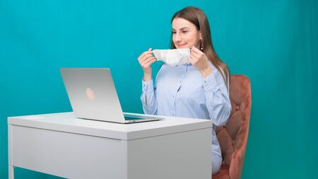 Female puts on a protective mask while working on a laptop in the workplace or at home during a pandemic. The concept of work during quarantine and self-isolation Imagens - 144865378