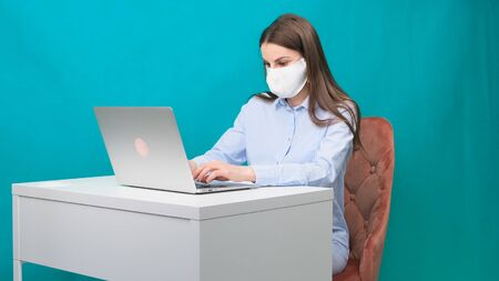 woman working at home with medical mask on face. coronavirus quarantine remote home working concept