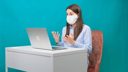 female in a protective mask is talking via video link on a laptop at the workplace or at home during a pandemic. The concept of work during quarantine and self-isolation Imagens