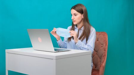 Female puts on a protective mask while working on a laptop in the workplace or at home during a pandemic. The concept of work during quarantine and self-isolation