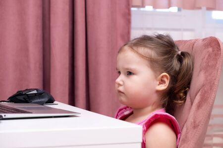 beautiful cute little girl behind laptop computer. The concept of online learning with a laptop, distance learning, self-education.
