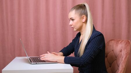 Woman is using laptop while sitting at her desk. Young european businesswoman is sitting in the office and working on notebook software Imagens