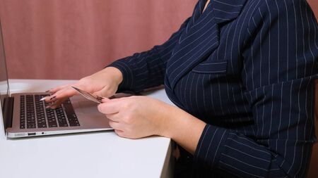 female hands make a purchase on the Internet using a laptop, payment by card, close-up Imagens