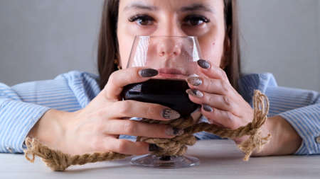 sad female looking wine glass tied with jute rope. The concept of alcohol addiction. The problem of alcoholism treatment.