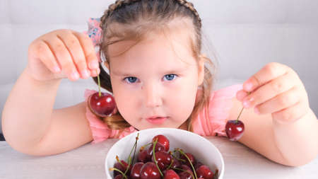 little girl sitting at a light wooden table with a plate of cherries and eating a berry. Healthy eating