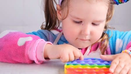 cute little girls with   sensory toy . little female presses colorful rainbow squishy soft silicone bubbles on white background. Stress and anxiety relief. Trendy fidgeting game