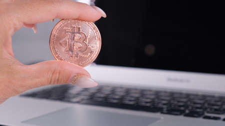 female hand holds Golden Cryptocurrency bitcoin with Notebook. Blurry of a Laptop and Cyrptocurrency Bitcoin Computer. business of money digital concept