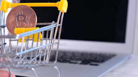 Small shopping cart with gold Bitcoin on it on the background of a laptop. Suitable for concepts as online shopping with bitcoins or investment and exchange sites.