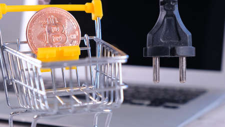 golden cryptocurrency Bitcoin power supply socket. Hand holding plug have computer monitor in the back, Concept Unplug bitcoin machine in the downtrend. BTC cryptocurrency, which is mined with high power consumption due to processing volume. The gold coin is very expensive
