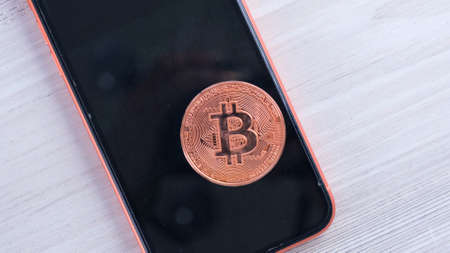 smartphone with bitcoin coin for shopping on a light background. Online shopping concept, blockchain, crypto mining.