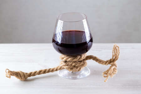 glass of red wine is tied with a rope. The concept of alcohol addiction Imagens