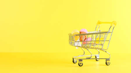 Shopping cart with ice cream inside on a yellow background, closeup. Black Friday Shopping and Discount Concept Imagens